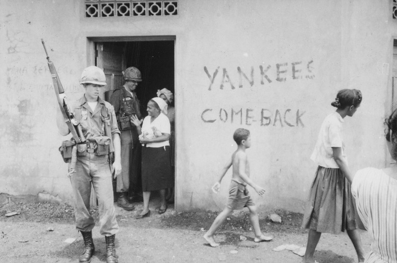 lossy-page1-800px-Food_distribution_in_front_of_-Yankees_come_back-_sign,_Santo_Domingo,_May_9.,_1965_-_NARA_-_541807.tif.jpg